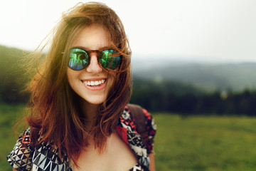 stylish woman traveler with fashionable sunglasses and windy hai