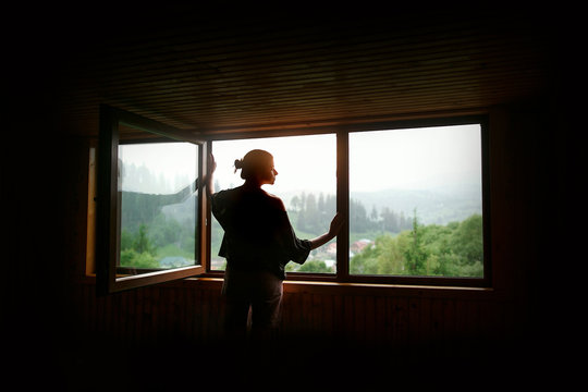 silhouette of woman in sunshine at big wooden window with view o