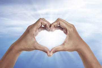 heart shaped hand with blue sky background