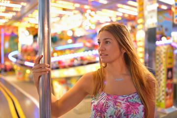 Happy girl standing on carousel
