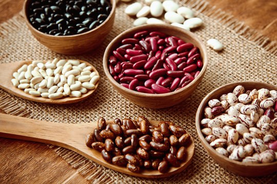 Beautiful multi-colored beans in bowls and wooden spoons on a background of burlap