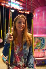 Pretty girl in denim jacket having fun on carousel