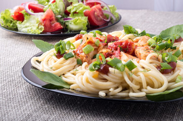 Home-cooked meals on a gray mat - pasta and vegetable salad