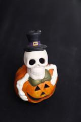 Halloween skeleton on pumpkin, dark wooden background