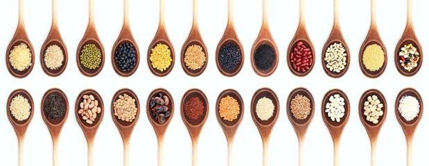 Various kinds of rice and legumes in wooden spoons