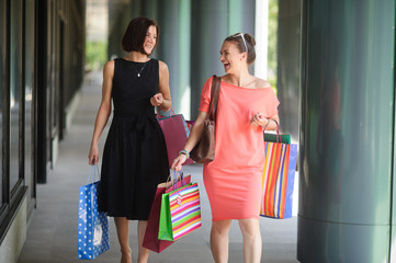 Two beautiful young women go with purchases.