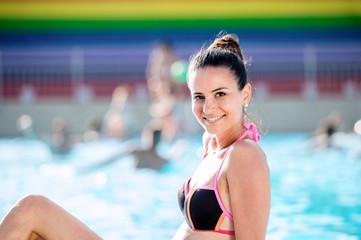 Woman in bikini sunbathing in aquapark. Summer heat and water.