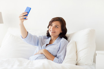 pregnant woman taking smartphone selfie at home