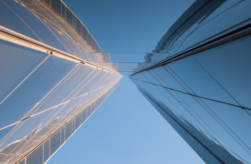 Urban Geometry, looking up to glass building. Modern architecture, glass and steel. . Abstract architectural design. Inspirational, artistic image.Minimal art.  Blue sky background. Minimalist.
