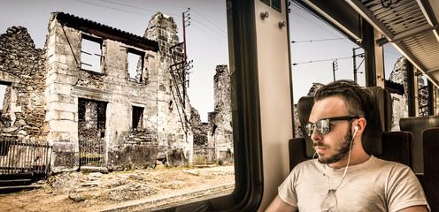 giovane uomo che vede la città distrutta attraverso il finestrino