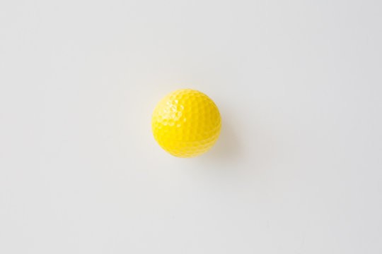 close up of yellow golf ball over white background