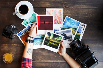 Women's hands holding printed photos. Dressed in red shirt, lotus tattoo on arm. On old wooden table scattered photos, two old medium format film camera, glass of juice, cup of coffee. Point of view