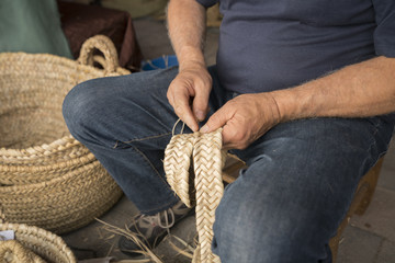 hand man weaving a wicker basket