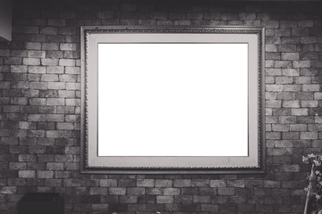Blank antique picture frame on brick wall, vignetting around (bl