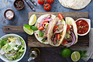 Steak tacos with sliced meet, salad and tomato salsa