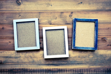 Blank black, gray and white wooden frames on wood background