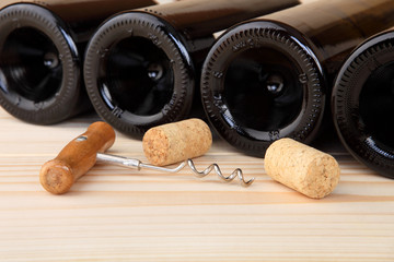 Corkscrew, corks and bottles of wine. Selective focus