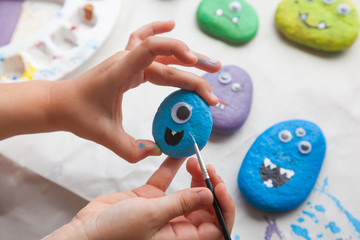 Child painting a stone for making a monster craft