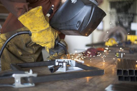 Welder welding steel stool support to each other.