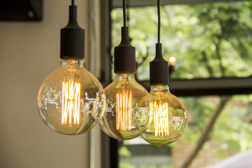 Glowing retro light bulbs hanging from ceiling