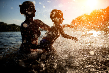 mother swim with baby in blue water at sunset;