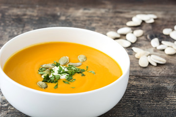 Pumpkin soup with cream and pumpkin seeds on wooden background