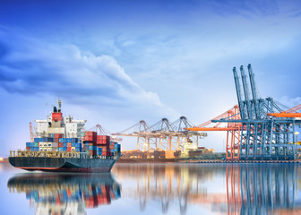 Logistics and transportation of International Container Cargo ship with working crane bridge in seaport for logistic import export background and transport industry. Wall mural