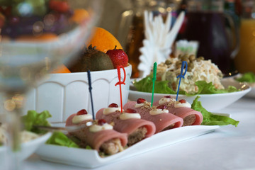 Appetizer of rolls with ham on the holiday table. Cold appetizers Banquet dinner served. Festive feast and food.