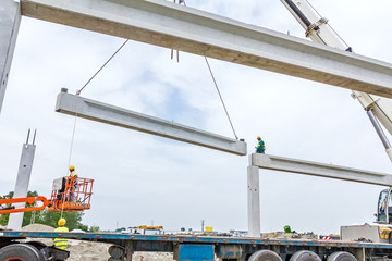 Mobile crane is unloading concrete joist from truck trailer