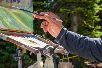 Artist's Hand with Paint Brush Painting with an Oil Palette a Mountain Wildflower Landscape on Canvas on an Easel en Plein Air