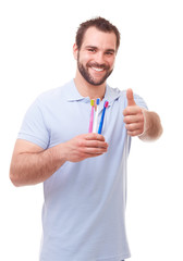Happy man holding toothbrushes