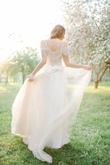Young beautiful bride portrait in park with flowers