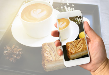Woman hand holding cellphone taking photo of coffee and dessert.