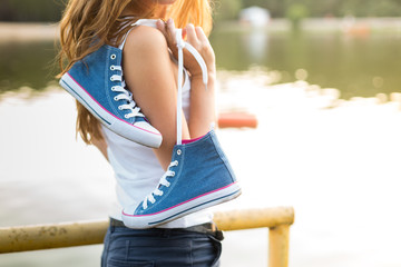 Tied pair of sneakers hanging on a girl