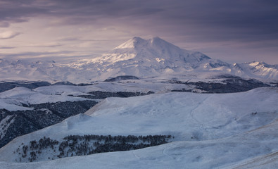 Mountain Elbrus in the winter in the rays of the dawn sun.