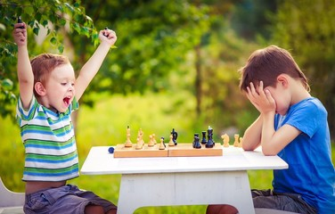 vivid emotions after the game of chess. two young chess players outdoors. boy rejoices won a game of chess. sad opponent covered his face, and upset losing