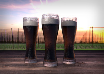 three glasses of dark beer with hop-garden background - 3D render