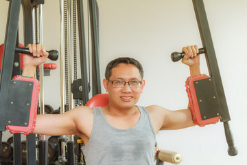 Asia man middle aged training arm equipment in the gym for strength, weight loss.