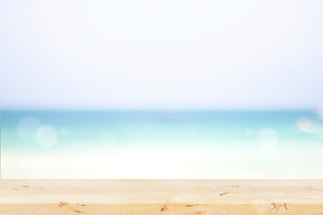 Wooden table with defocused blue sea, white sand beach background.