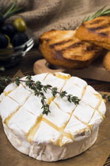 Camembert cheese with thyme and toasted bread on a wooden board