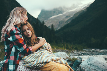 Mom with daughter wrapped in blanket