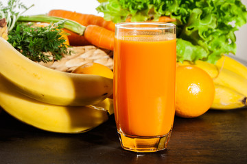 Glass of fruit juice with orange, carrots and banana