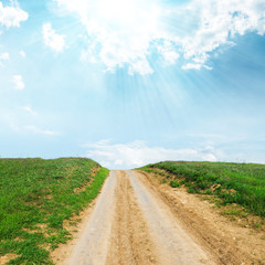 rural road in green grass to sun in blue sky