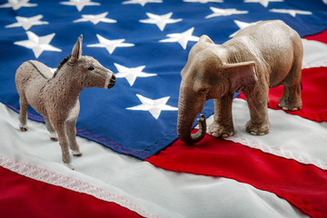 Democrats vs republicans are facing off in a ideological duel on the american flag. In American politics US parties are represented by either the democrat donkey or republican elephant
