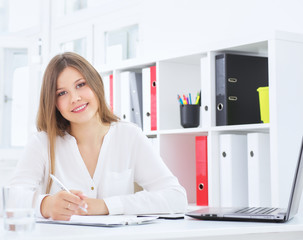 Portrait of a young secretary at the desk in the modern office.