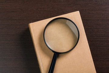 Magnifying glass and book o the wooden background