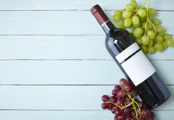 A bottle of red wine with bunches of grapes on a blue painted wooden table top background, arranged to form a page border