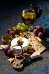 Camembert cheese, snacks and glasses of wine, vertical