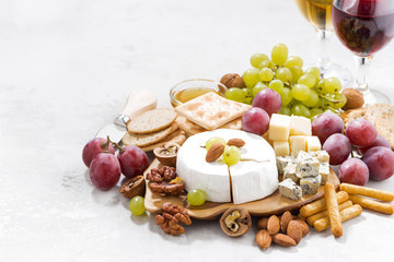 camembert, grapes, wine and snacks on a white table