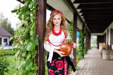 woman in national ukrainian traditional costume holding a clay jug and welcoming guests